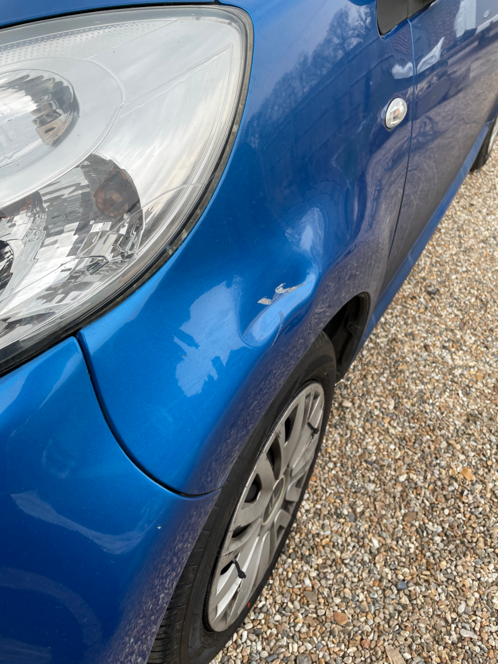 scuff mark and minor dent on car before repair